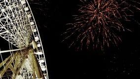 Helder Ferris Wheel in de nacht met grote Vuurwerkachtergrond stock footage