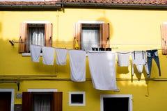 Helder geel huis met blinden en was het hangen uit op het Eiland Burano, Venetië royalty-vrije stock afbeelding