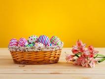 Helder gekleurde eieren met bloemen in een rieten mand Stock Fotografie