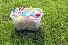 Helder gekleurde wasknijpers in een emmer op groen gras in sunsh Stock Afbeeldingen