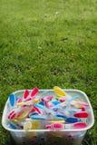 Helder gekleurde wasknijpers in een emmer op groen gras in zon Stock Foto