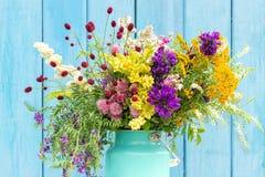 Helder kleurrijk boeket van wilde bloemen in het blikvaas van het starmtin op blauwe houten raad als achtergrond Malplaatje voor  royalty-vrije stock afbeeldingen