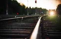 Helder licht van de koplampen van de naderbij komende trein, die op sporen met houten dwarsbalken berijdt stock foto's