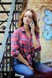 Helder meisje in plaidoverhemd die op de telefoon spreken Stock Afbeelding