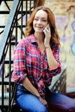 Helder meisje in plaidoverhemd die op de telefoon spreken Stock Afbeeldingen
