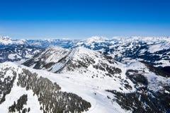 Helder panorama van bergketens met sneeuw en ijs op de bovenkanten tegen de blauwe hemel in de winter en dichte bossen royalty-vrije stock foto's