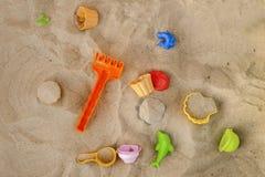 Helder plastic kinderen` s stuk speelgoed in het zand Kinderen` s speelgoed voor t royalty-vrije stock foto's