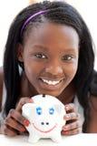 Helder tienermeisje dat een piggy-bank houdt stock foto's
