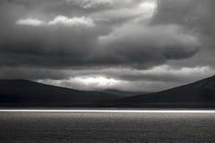 Helder zonlicht bij gouden uur op groot meer met dramatische en humeurige zwart-witte landschapsachtergrond Stock Foto's