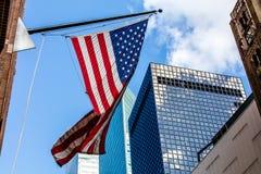 Heldere Amerikaanse vlag en skyscrappers in een zonnig weer Stock Foto