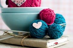 Heldere ballen van garen in blauwe die platen en hart van gevoeld wordt gemaakt Royalty-vrije Stock Afbeeldingen