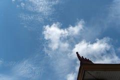 Heldere blauwe hemel met een paar die cumulus en van de altcumulus wolken, met typische Balinese huisornamenten worden verfraaid stock fotografie