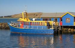Heldere bue en gele boot tegen een blauw en geel gebouw Royalty-vrije Stock Foto