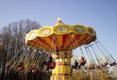Heldere carrousel met kettingen die rond in het park met de kinderen spinnen Het onduidelijke beeld van de motie stock foto's