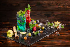 Heldere cocktails met munt, kalk, ijs, bessen en carambola op het zwarte bureau Koele de zomerdranken voor partijen De ruimte van Stock Fotografie