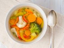 Heldere de lente groentesoep met bloemkool, broccoli, peper, wortel, groene erwten Hoogste mening, witte houten achtergrond royalty-vrije stock foto