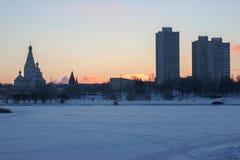 Heldere de winterochtend heldere scharlaken zonstijgingen op de horizon wegens de huizen en de Kerk ijzig duidelijk weer op stock afbeelding
