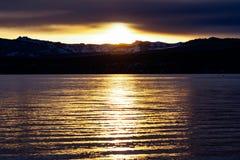 Heldere die zonsondergang op de oever van Meer Tahoe, Siërra Bergen in sneeuw zichtbaar op de achtergrond worden behandeld; Calif royalty-vrije stock afbeelding