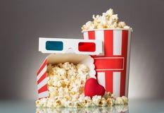 Heldere doos met popcorn, 3D glazen en een hart op grijs Stock Foto