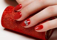 Heldere feestelijke rode manicure op vrouwelijke handen Spijkersontwerp Royalty-vrije Stock Afbeeldingen