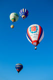 Heldere gekleurde ballonsvlieg in blauwe hemel Stock Foto's