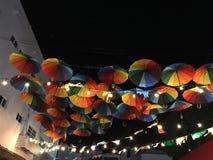 Heldere gekleurde die paraplu's, in alle primaire kleuren van het palet, tegen de achtergrond van de donkere nachthemel worden ge stock afbeelding