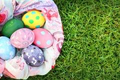 Heldere gekleurde eieren en mooie doek op gras op Pasen-dag Royalty-vrije Stock Fotografie