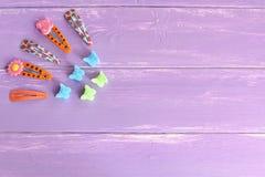 Heldere gekleurde haarklemmen voor meisjes op lilac houten achtergrond met exemplaarruimte voor tekst De achtergrond van de meisj Royalty-vrije Stock Afbeelding