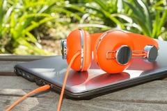Heldere gekleurde oranje hoofdtelefoons en mobiele compu Royalty-vrije Stock Foto's