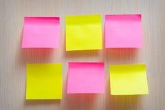 Heldere gele en roze stickers op een houten achtergrond Stock Afbeeldingen