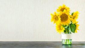 Heldere gele grote zonnebloemen in glasvaas op donkere lijst aangaande ligh royalty-vrije stock foto