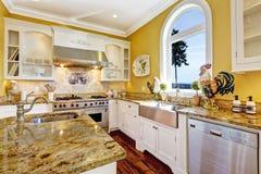 Heldere gele keukenruimte met granietbovenkanten en boogvenster Stock Afbeeldingen
