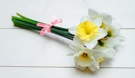 Heldere gele gele narcissen op witte houten lijst, selectieve nadruk Gele en witte narcissen De kaart van de groet Stock Fotografie