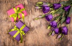 Heldere giftdozen met linten en purpere bloemen Een boeket van eustoms en een romantische gift Stock Afbeeldingen