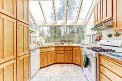 Heldere keukenruimte met glasmuur en plafond Stock Afbeelding