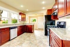 Heldere keukenruimte met zwarte en staaltoestellen Stock Afbeeldingen