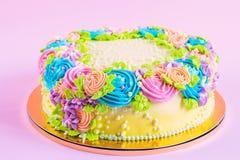 Heldere kleurrijke die cake met roombloemen wordt verfraaid Stock Afbeeldingen