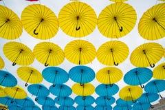 Heldere kleurrijke gele en blauwe paraplu'sachtergrond Royalty-vrije Stock Afbeelding