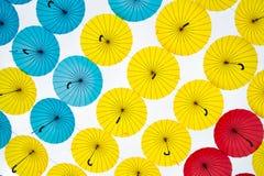 Heldere kleurrijke gele, rode en blauwe paraplu'sachtergrond Stock Foto's