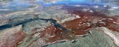 Heldere kleurrijke natuurlijke abstractie: een zandtextuur op de rode kust van zout meer, blauw, groen, geel, wit, kleur die int. Stock Foto