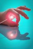 Heldere lichtbron over het eind van de sonde tussen groot en wijsvingers de linkerhand de persoon Stock Foto