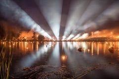 Heldere lichte buizen over een meer met bosbrand op achtergrond Stock Foto