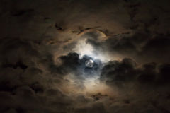 Heldere maan in de donkere hemel die rond gezwollen wolken gluren Stock Fotografie