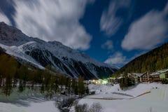 Heldere maanlicht verlichtende bergen en de wintervallei stock foto's