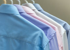 Heldere mensen` s overhemden die op hangers grijze achtergrond hangen Royalty-vrije Stock Afbeeldingen