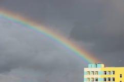 Heldere multi-colored brede kleurrijke regenboog na het onweer in de grijze hemel boven de rijtjeshuizen Royalty-vrije Stock Fotografie