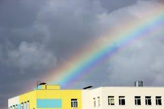 Heldere multi-colored brede kleurrijke regenboog na het onweer in de grijze hemel boven de rijtjeshuizen Stock Afbeelding