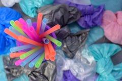 Heldere multi-colored plastic buisjes in een purper glas op de achtergrond van vuilniszakken royalty-vrije stock fotografie