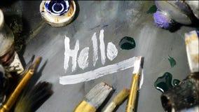 Heldere olieverven in een buis op een vuil palet Verf in gebruik Getrokken, geschreven Hello stock videobeelden