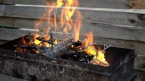 Heldere oranje brandbrandwonden in de zwarte close-up van de metaalgrill stock footage